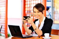 Femmina sveglia al caffè per mezzo del cellulare e del computer portatile Fotografia Stock
