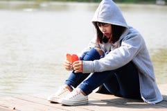 Femmina triste con cuore di carta rosso Fotografie Stock Libere da Diritti