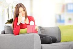 Femmina triste messa su un sofà che la pulisce occhi dal gridare con i tis immagine stock
