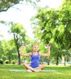 Femmina in un parco che si siede su una stuoia e che si esercita con le teste di legno Fotografia Stock