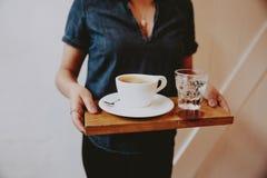 Femmina in una camicia tagliata bassa che tiene un vassoio di legno con caffè e acqua frizzante su  immagine stock