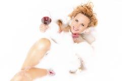 Femmina in vasca spumosa riempita di petali Tenuta del vetro di vino rosso Immagini Stock