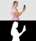 Femmina in vestito rosa che fa video chiamata con il suo Smart Phone, Alpha Channel fotografie stock libere da diritti