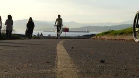 Femmine di Silhouettesmales che rollerblading le biciclette di guida archivi video