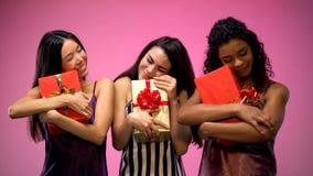 Femmine interrazziali in regalo della tenuta dei pigiami, celebrante festa, felicit? fotografia stock libera da diritti