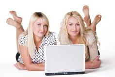 Femmine sorridenti con il computer portatile fotografia stock