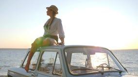 Femminile all'automobile d'annata su fondo del tramonto e sulla conversazione sul telefono cellulare, giovane femmina alla vecchi archivi video