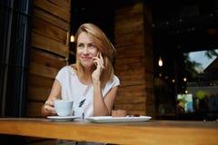 Femminile caucasico splendido avendo conversazione telefonica delle cellule mentre sedendosi alla tavola di legno con il dessert  Fotografie Stock Libere da Diritti
