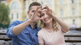 Femminile e maschio che si siedono vicino ad a vicenda, mettendo sul cuore a forma di dito stock footage