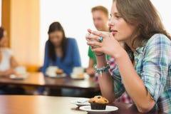 Femminile mangiando caffè e muffin alla caffetteria Fotografia Stock Libera da Diritti