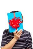 Femminile nasconda il suo fronte dietro il contenitore di regalo Immagine Stock