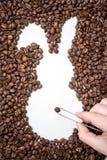 Femminile passi con le pinzette che presentano i chicchi di caffè e crea la forma di un coniglietto di pasqua fotografie stock libere da diritti