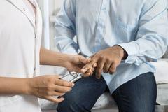 ` Femminile s Sugar Level With Glucometer del dottore Examining Patient fotografia stock libera da diritti