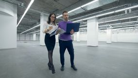 Femminili e gli specialisti maschii di un'architettura stanno camminando lungo la costruzione stock footage