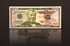 Femtio dollar med ryska rubel för reflexion hundra Arkivbild