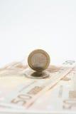 Femtio euroanmärkningar fläktade en och två euromynt royaltyfri foto