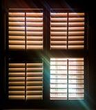 Fenêtre à volets avec un laisser ouvert de carreau par des rayons de lumière et d'une image faible des feuilles d'automne dehors photos stock