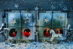 Fenêtre atmosphérique de Noël avec les bougies rouges extérieures avec la neige Idée pour une carte de voeux Image libre de droits