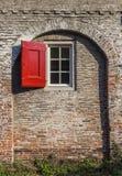 Fenêtre avec le volet rouge dans le mur médiéval de ville d'Amersfoort Photo stock