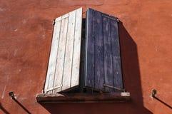 Fenêtre avec les abat-jour en bois du soleil sur le mur de terre cuite Image stock