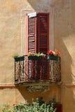 Fenêtre avec les abat-jour en bois et balcon avec des fleurs, italiennes Image libre de droits