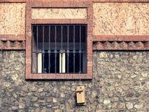 Fenêtre avec ron râpant sur une façade rustique Photos libres de droits