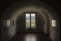 Fenêtre avec un gril sur une fenêtre arquée dans une chambre noire Photographie stock libre de droits