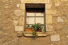 Fenêtre avec un pot de fleurs dans un village espagnol Images stock