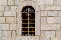 Fenêtre avec un trellis dans le mur en pierre de la vieille forteresse Photos libres de droits