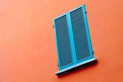Fenêtre bleue sur le mur orange Images stock