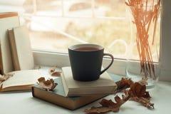 Fenêtre confortable avec des feuilles d'automne, un livre, une tasse de thé, heure de lire, concept de week-end d'automne Photos libres de droits