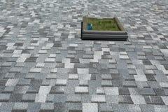 Fenêtre d'installation sur les nouveaux bardeaux d'asphalte de toit Nouvelle maison en construction photographie stock
