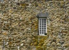 Fenêtre dans le vieux mur de roche Photos stock