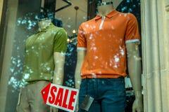 Fenêtre de boutique avec la flèche masculine habillée de mannequins et de signe de vente images stock