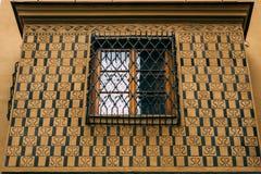 Fenêtre de cadre en bois derrière le gril en métal sur le mur ornemental de l'ol Photographie stock
