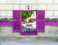 Fenêtre de café avec les volets et les fleurs violets sur le rebord de fenêtre photo libre de droits
