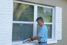 Fenêtre de calfeutrage de propriétaire d'une maison protégeant contre les intempéries à la maison contre l'eau et des tempêtes de Images stock