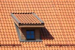 Fenêtre de grenier dans le toit carrelé orange images stock