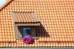 Fenêtre de grenier dans le toit carrelé orange image stock