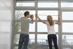 Fenêtre de mesure d'appartement de couples Image stock