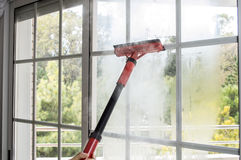 Fenêtre de nettoyage avec la vapeur Photographie stock libre de droits
