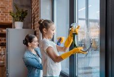 Fenêtre de nettoyage de mère et de fille à la maison image stock