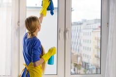 Fenêtre de nettoyage de femme à la maison photo stock