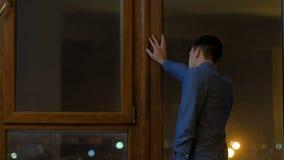 Fenêtre de regard à la maison debout de attente de jeune homme banque de vidéos