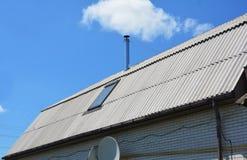 Fenêtre de toit de lucarne de grenier sur le toit de maison d'amiante avec le fond de ciel bleu Images stock