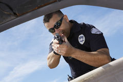 Fenêtre de voiture d'Aiming Gun Through de policier Photographie stock