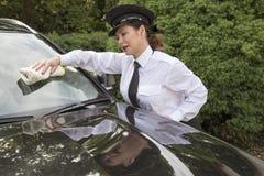 Fenêtre de voiture de polissage de chauffeur de femme Photographie stock libre de droits