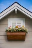 Fenêtre en bois avec la fleur au toit de la maison Photos libres de droits
