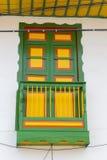 Fenêtre en bois jaune et verte d'un avant colonial de maison dans la vente Photo stock