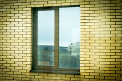 Fenêtre en plastique de Brown dans une maison de brique photos libres de droits